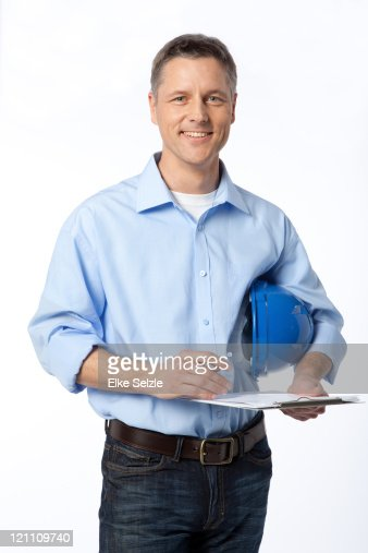 Man holding clipboard and hard hat : Stock Photo