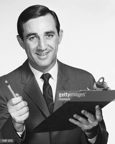 Mann hält Zwischenablage und Bleistift