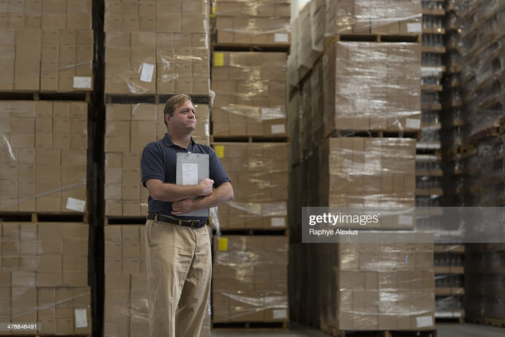 Man holding clipboard in warehouse : Stock Photo
