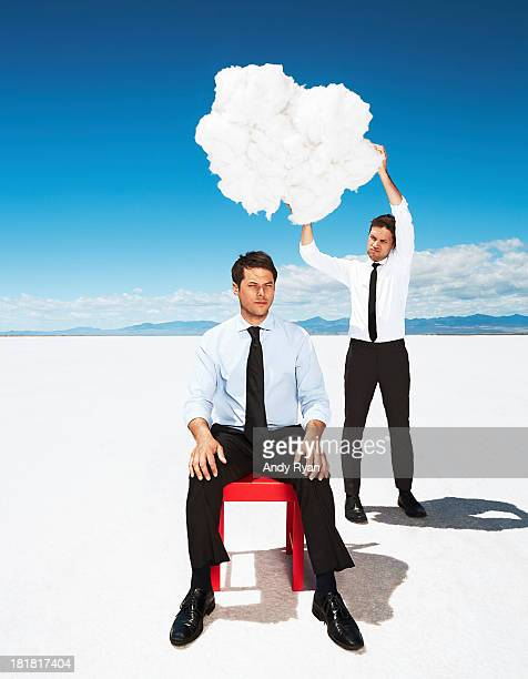Man holding cloud over colleague's head in desert.