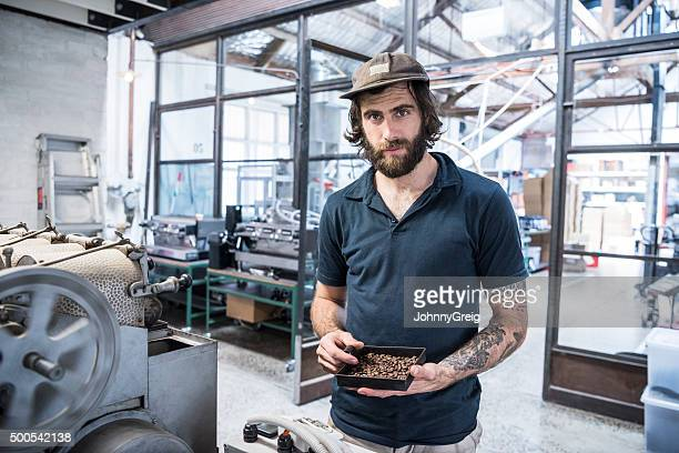 Man holding coffee beans in coffee roasting warehouse, portrait