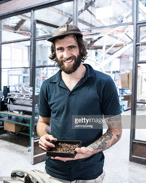 Man holding coffee beans in coffee roasting warehouse smiling, portrait