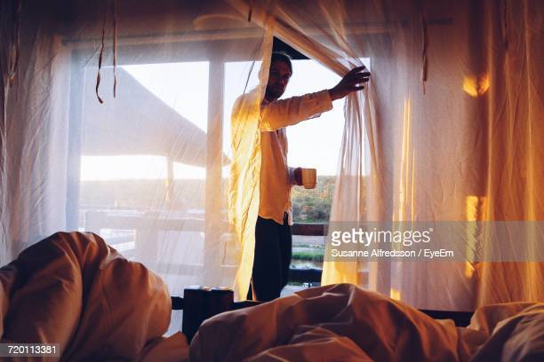 Man Holding Coffee Cup Looking Through Curtain At Home