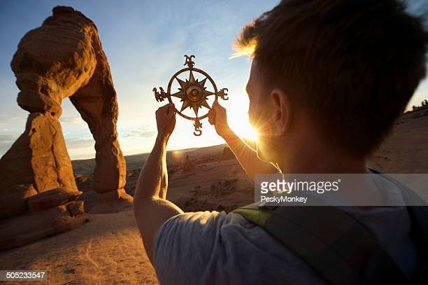 Man Holding Compass Rose at Sunset Arch