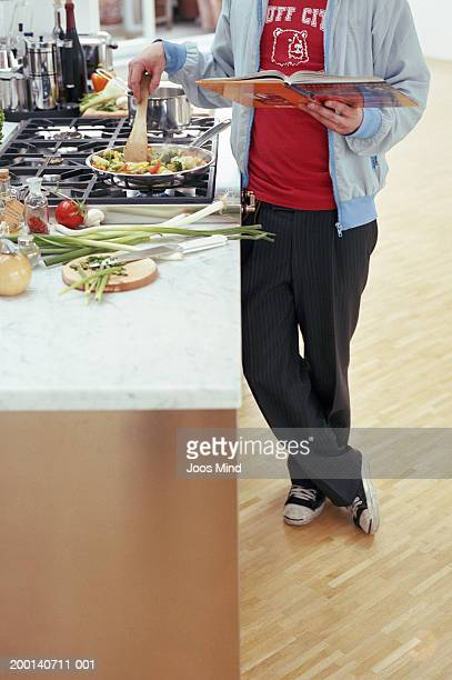 Man holding cookbook, stirring vegetables in frying pan, low section