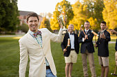 Man holding croquet trophy on lawn