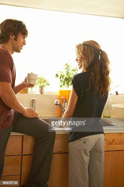 Man holding cup of coffee and woman washing dishes