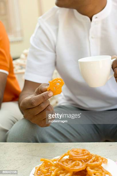 Man holding cup of tea and snack