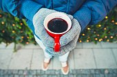 Man holding cup of the hot wine at the Christmas market - Munich, Germany - selective focus