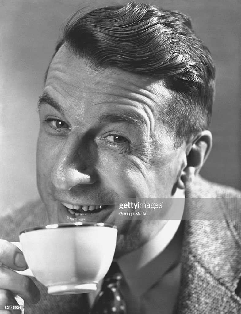 Man holding cup posing in studio, (B&W), close-up : Stock Photo