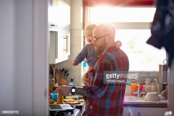 Man holding daughter whilst using laptop