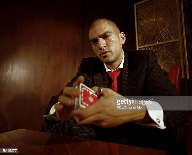 Man holding deck of cards, low angle view, portrait