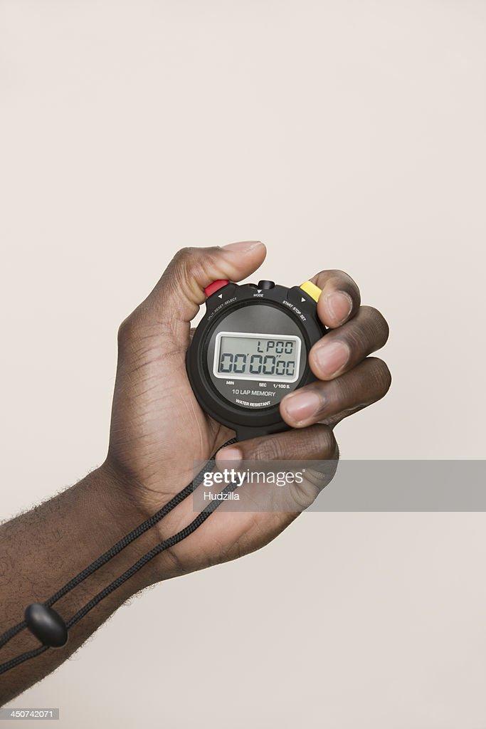 Man holding digital stopwatch