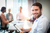 Portrait of man holding digital tablet while coworker interacting in the background in the office