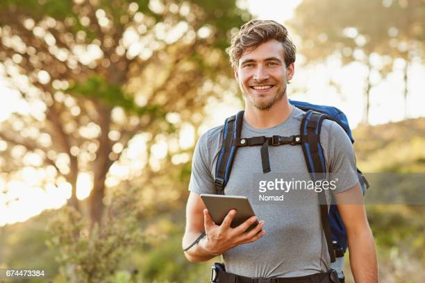 Man holding digital tablet while hiking in forest