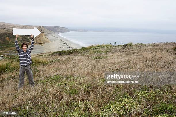 Man holding direction arrow near beach