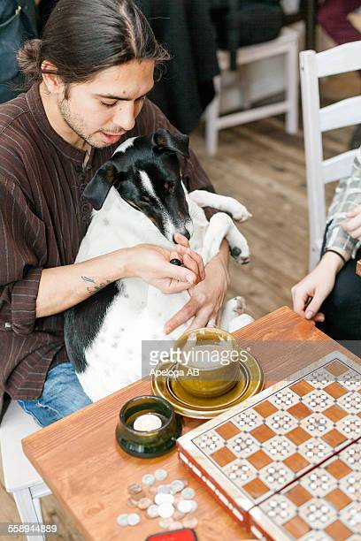Man holding dog while playing dice game at cafe