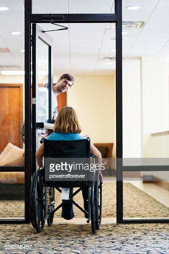 Man Holding Door for Disabled Girl in Wheelchair