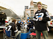 Man holding drinks at tailgate party, friends in background