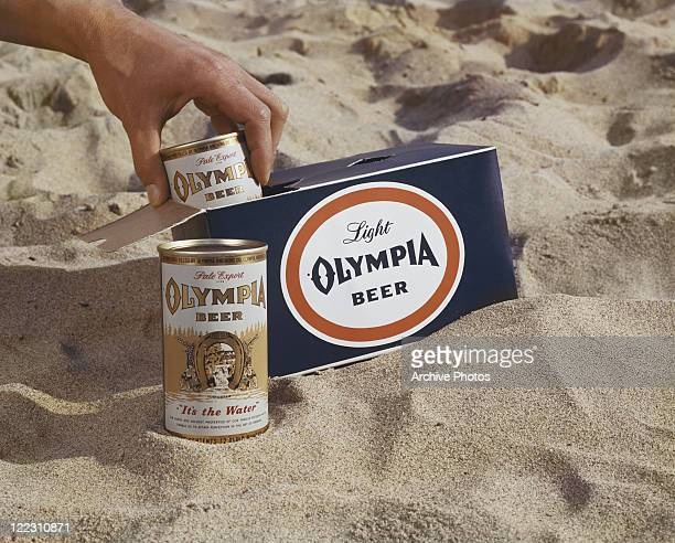 Man holding drinks can with box on sand, close-up