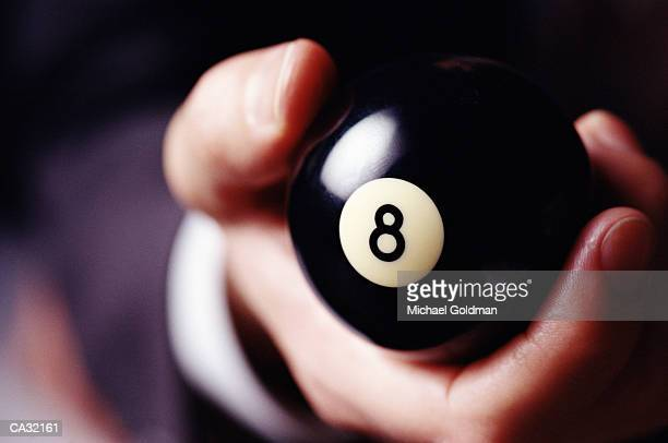 Man holding eight ball in hand, close-up