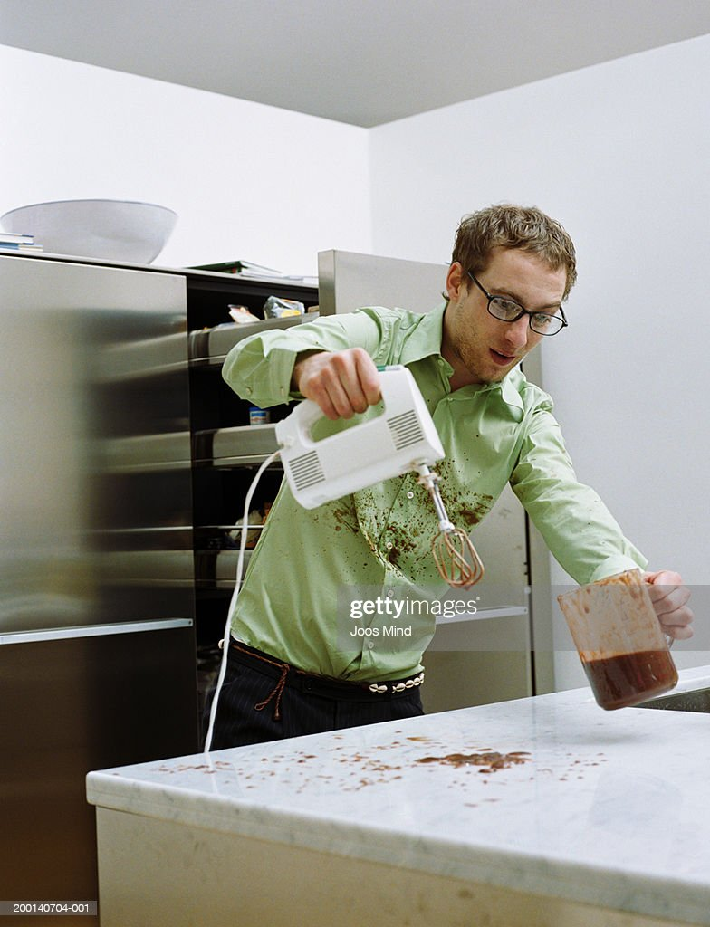Man holding electric mixer and jug, contents of jug spilt on counter : Stock Photo