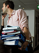 Man holding files, colleague holding telephone receiver to his head