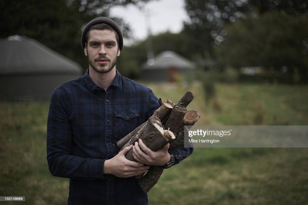 Man holding firewood on glampsite. : Stock Photo