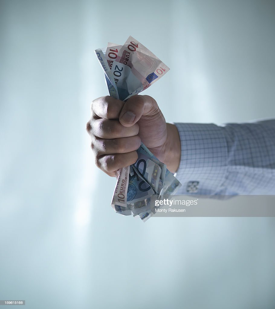 Man holding fistful of euro notes