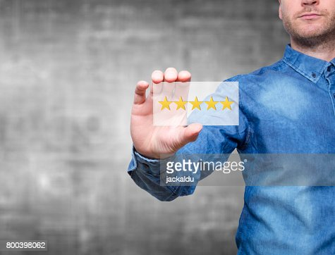 Man holding five star rating. Five stars service. Grey background - Stock Image : Stock Photo