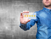 Man holding five star rating. Five stars service. Grey background - Stock Image