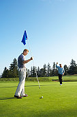 Man holding flag, other golfer putting