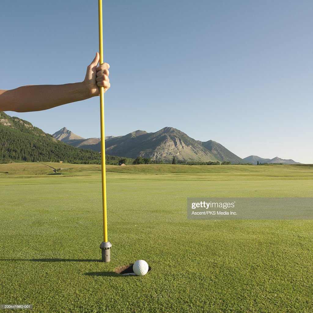 Man holding flag pole by golf ball rolling into hole, close-up