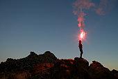 Man holding flare at sunset.