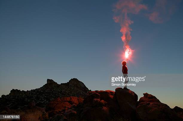 Man holding flare at sunset.