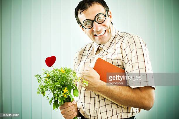 Man holding flowers and a notebook.