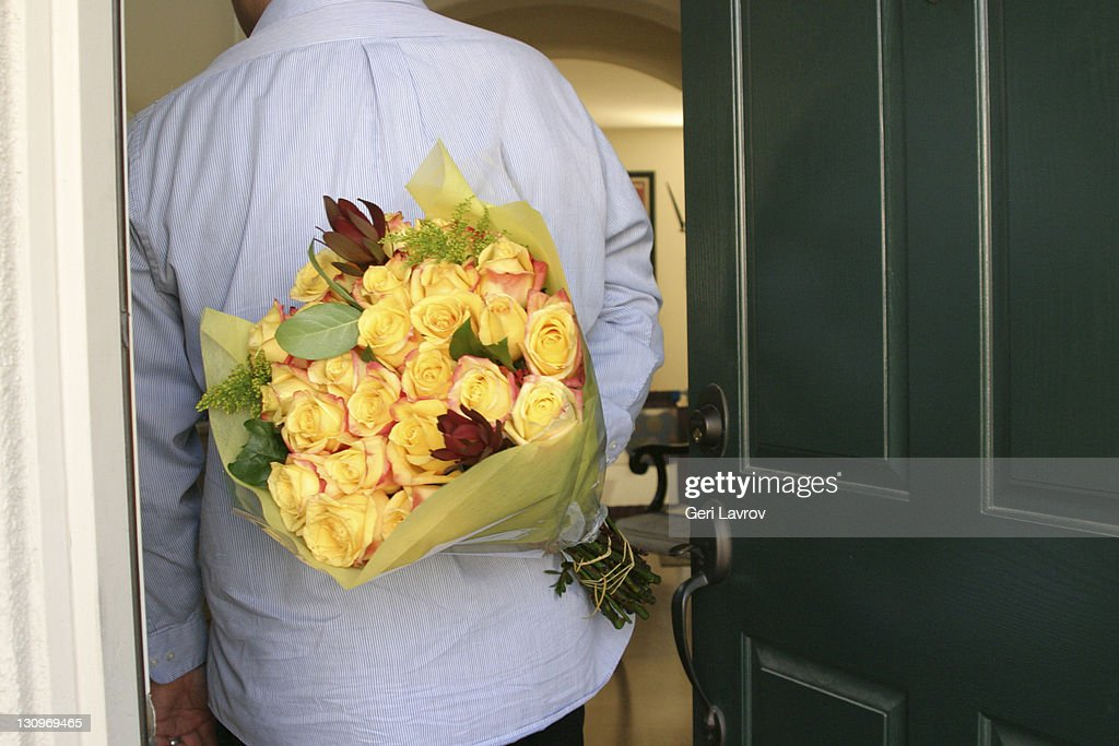 Man holding flowers behind himself : Stock Photo
