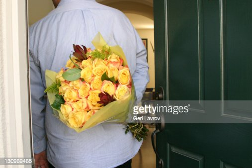 Man holding flowers behind himself : ストックフォト