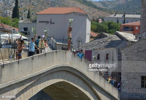 A man holding flowers in his hand jumps into the Neretva river from historical 'Old Bridge' also known as 'Mostar Bridge' to mark the 22nd...