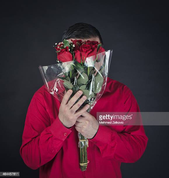 Man holding flowers over his face