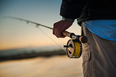 Sunrise over the marsh with man holding a fly rod and reel