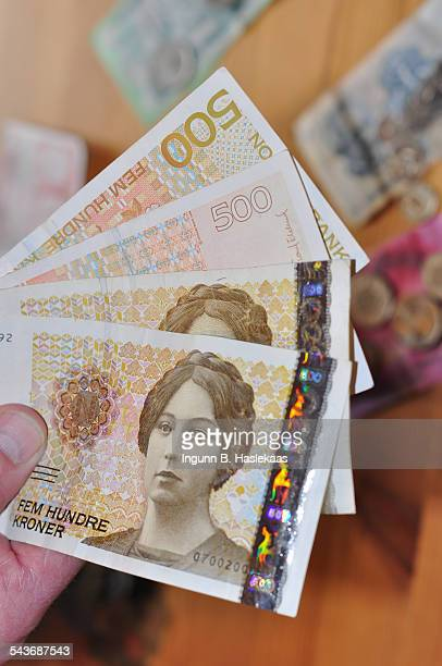 Man holding four 500 norwegian krone banknotes Variety of foreign currency on the background table
