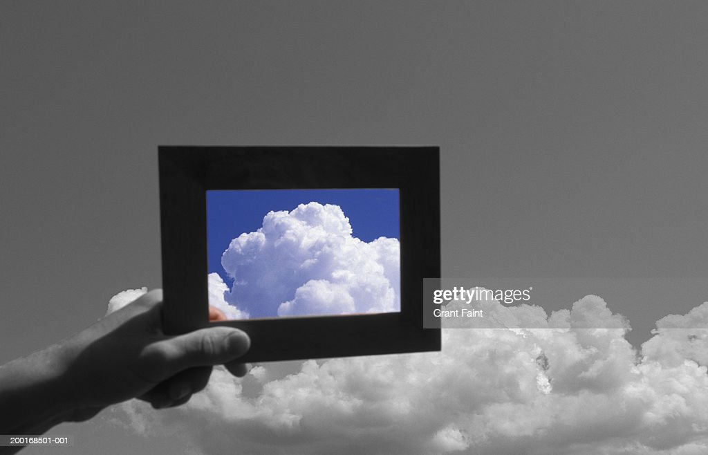 Man holding frame up to clouds (digital enhancements) : Stock Photo