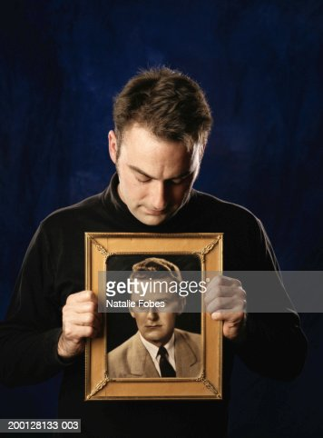 Man holding framed photograph of young man : Photo