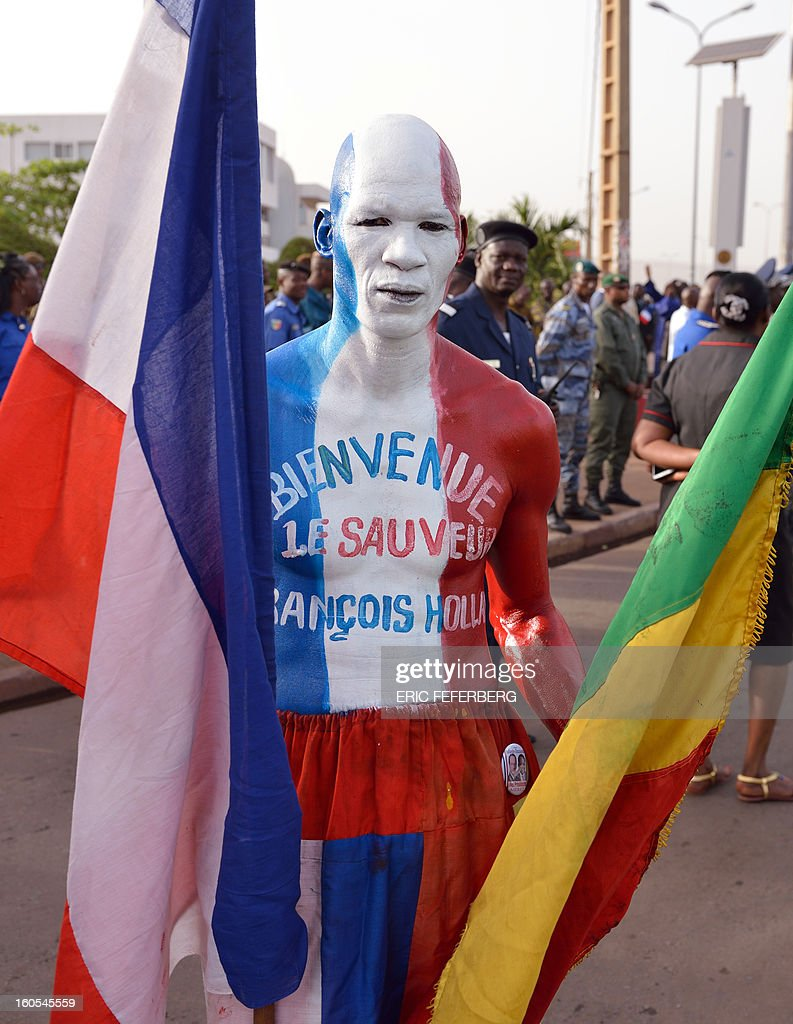 A man holding French and Malian national flags poses on February 2, 2013 at the Independence Square in Bamako, while French President and his Malian counterpart deliver a speech. French President Francois Hollande called on Africans to take over the fight against extremism as he received a rapturous welcome today in Mali, where a French-led offensive has driven back Islamist rebels from the north. The man's body is painted with blue, white and red, the French national colors and reads 'Welcome the Savior, Francois Hollande'.