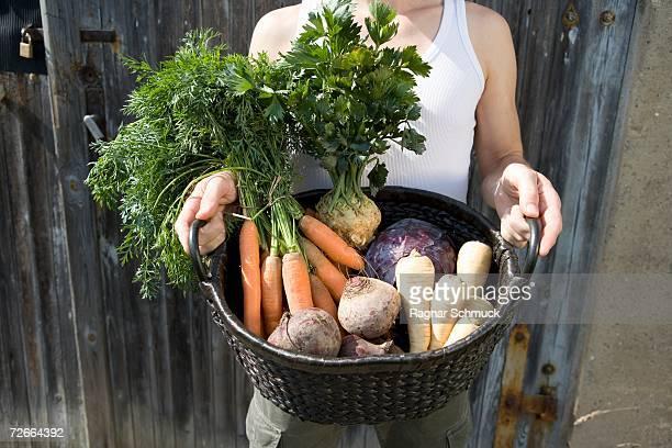 Man holding freshly picked vegetables in basket