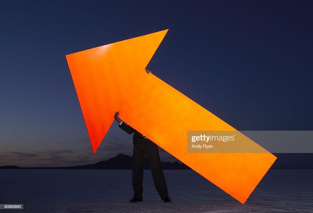 Man Holding Giant Reflective Arrow, Salt Flats  : Stock Photo