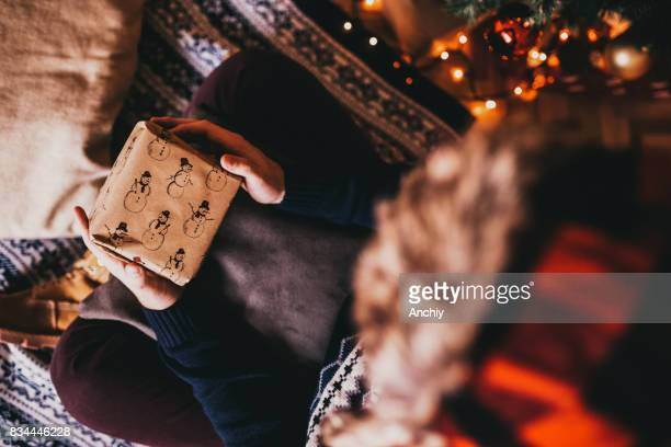 Man holding gifts in front of Xmas tree