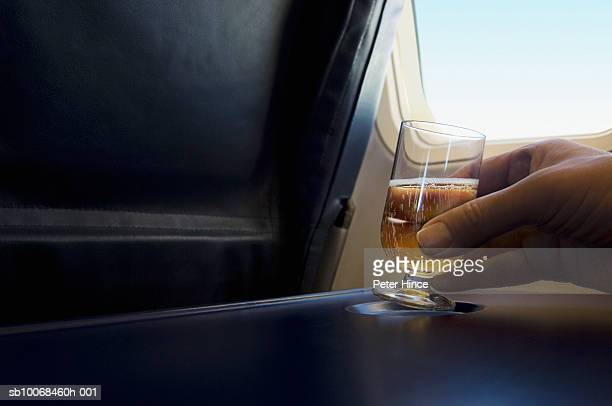 Man holding glass of champagne on table on airplane, close up of hand