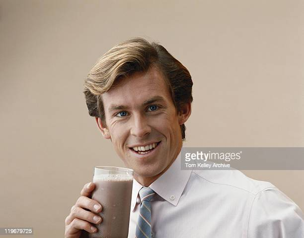 Man holding glass of drink, smiling portrait